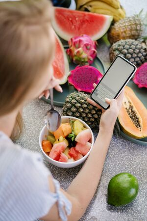 Concept of healthy and seasonal nutrition. Vertical and high angle view of young adult woman using modern smartphone with copy space on display, standing on kitchen, eating fruit salad