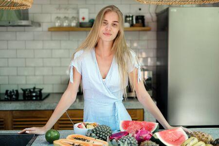 Healthy and seasonal food concept. Smiling young adult girl standing on kitchen near table with fruits, prepare cooking juicy and detox salad