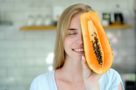 Concept of summer and seasonal food. Portrait view of carefree young adult woman covered half face with papaya fruit, smiling wide and standing on kitchen with copy space Banco de Imagens