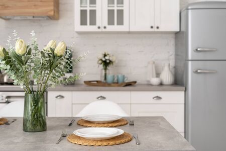 Cozy kitchen at house with modern interior, flowers in vase at setting dining table, plates and cutlery, silverware against new furniture, white wooden cabinets and countertop on blurred background Banco de Imagens