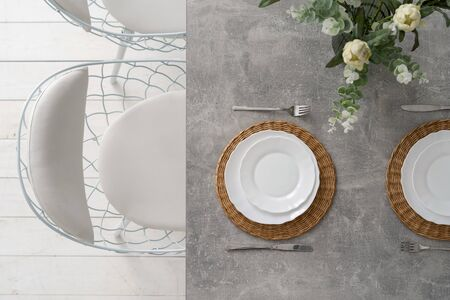 Top view of table setting at dining room with plates, cutlery, silverware and flowers in vase. Concept of fancy element in kitchen interior at modern house
