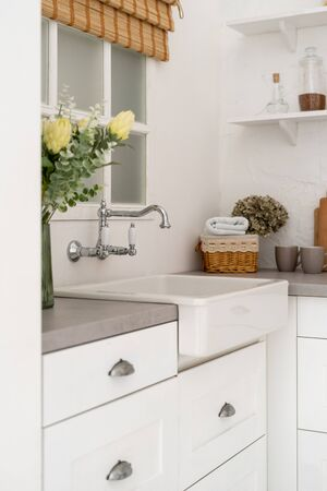 Vertical photo of element in kitchen interior with bright modern style, flowers on countertop and sink next to window Banco de Imagens