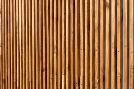 Selective focus at vertical wooden slats on wall in modern interior. Natural brown construction wood lath in line making texture pattern background with copy space Banco de Imagens