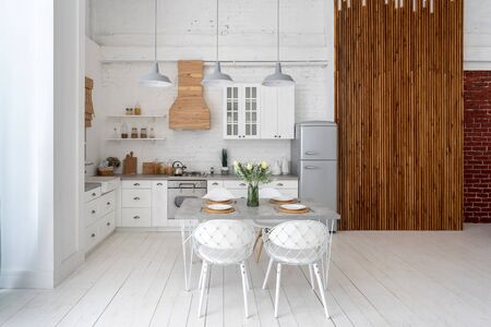 Front view of white kitchen with modern interior, cabinets, new furniture, dining table setting, gas stove, oven and refrigerator near wooden slat panel wall
