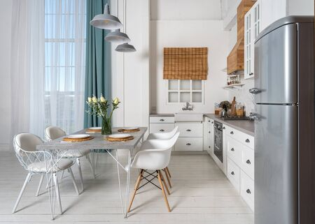 Kitchen interior in bright modern style with sink next to window, gas stove, oven, wooden cabinets, countertop and dining table setting near refrigerator