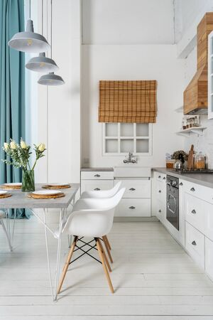 Vertical photo of fragment contemporary kitchen with modern interior style, dining table setting, gas stove, refrigerator, oven, wooden cabinets furniture and sink next to window