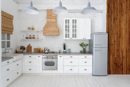 Front view of modern kitchen at apartment with white interior, new furniture, gas stove, oven, refrigerator, wooden cabinets, countertop, sink next to window and copy space on hardwood floor