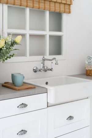 Vertical and side view photo of white kitchen interior in bright modern style. Countertop with cups near empty sink next to window Banco de Imagens
