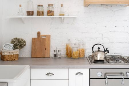 Fragment of kitchen interior in bright modern style with kettle on gas stove, countertop, furniture, wooden cabinets and glass jar full of cereal and spaghetti