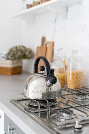 Vertical and selective focus on silver metallic kettle at gas stove. Fragment of contemporary kitchen with modern interior style and blurred background
