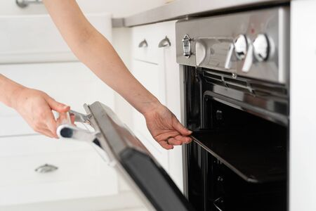Cropped view of woman hand open gas oven and taking cooking pan tray, standing at modern kitchen in apartment with white interior Banco de Imagens