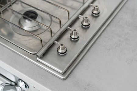 High angle view of fragment new metallic gas stove with regulator handles. Contemporary kitchen with modern interior style and copy space on countertop