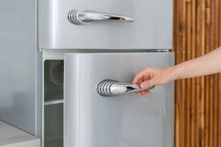 Cropped view of woman hand open fridge door, standing in contemporary kitchen with modern interior. Housewife using new refrigerator in dining room Banco de Imagens