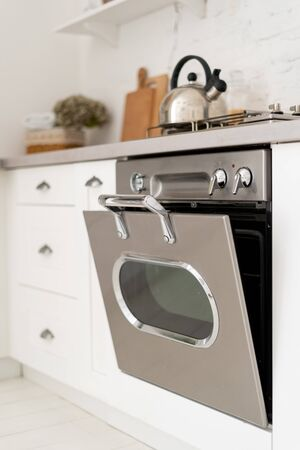 Vertical and selective focus of new silver gas oven with open door under stove. Element of contemporary kitchen with modern interior style and built in cooking appliance