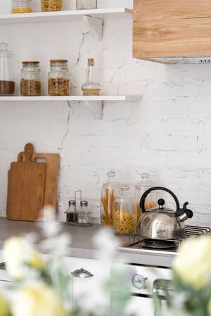 Vertical photo of metallic kettle on gas stove with boiled water for beverage. Conceptual and cozy kitchen at house in modern interior with pantry shelf on wall Banco de Imagens