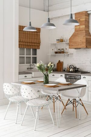 Vertical photo of white contemporary kitchen with modern interior style, furniture, setting table at dining zone, gas stove, oven, wooden cabinets, countertop and sink next to window Banco de Imagens