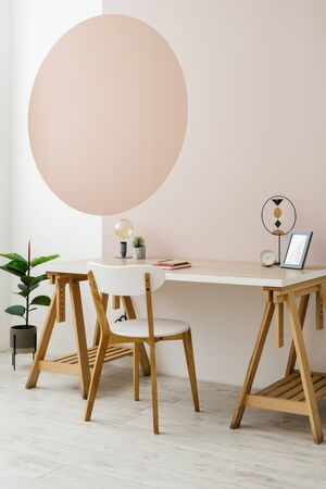 Vertical photo of modern interior room with wooden desk, decor, minimalist chair, houseplant on floor and geometric painting on wall with copy space Imagens - 148272271