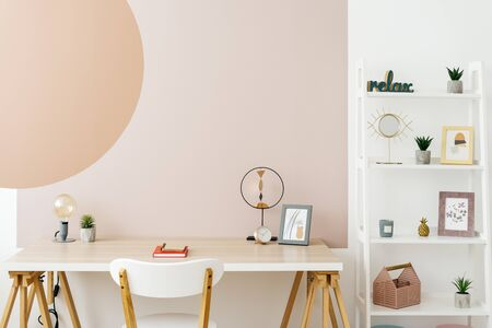 Concept of contemporary workplace. Modern room with minimal interior, decor at wooden table, shelves, chair and graphic painting on copy space wall