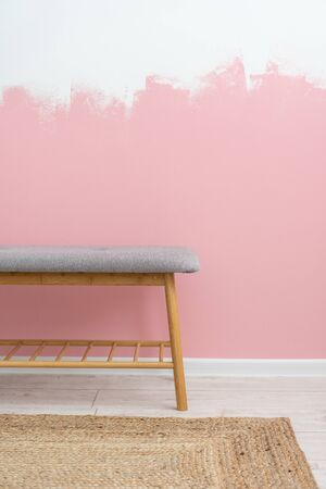 Concept of painting and redecoration lounge. Vertical photo of modern living room in renovated house with comfortable furniture, bench seat, woven rug, against pink wall on background