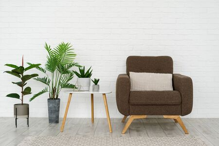 Modern living room in modern house with comfortable armchair, cushioned furniture, rug on floor, wooden triangular table, green houseplant in flowerpot against brick white wall with copy space Archivio Fotografico