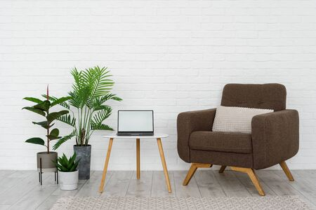 Minimalist interior of living room with cushioned furniture, comfortable armchair, wooden triangular coffee table, rug, mockup on display at laptop computer and green plants against white brick wall