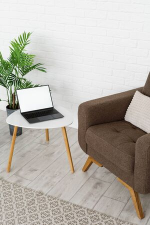 Vertical photo and high angle view of modern interior room with comfortable armchair, cushioned furniture, laptop computer with copy space on display and green plant on floor near textile rug