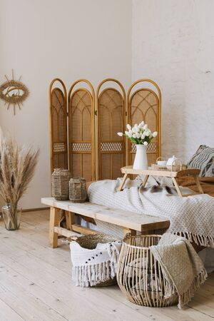 Vertical photo of comfortable bedroom in bohemian interior style with breakfast tray, flowers and textile sheet on bed, wooden bench seat, bamboo dressing screen, home decor in wicker basket