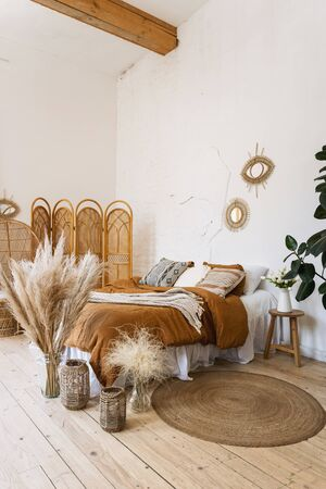 Vertical photo of comfort bedroom in boho style interior with pillow and plaid on bed, home decor in wicker basket, bamboo dressing screen, dry plants in vase
