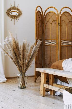 Vertical photo of cozy apartment in boho chic style interior with comfort bedroom, bamboo dressing screen near bed, home decor, dry plants in vase, mirror on white wall Stockfoto