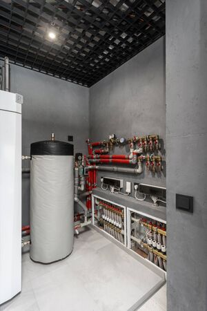 Vertical photo of technical boiler room in new modern house with filter on water tank capacity, pipes equipment, plumbing stuff and valves on electronic counter meter Banque d'images