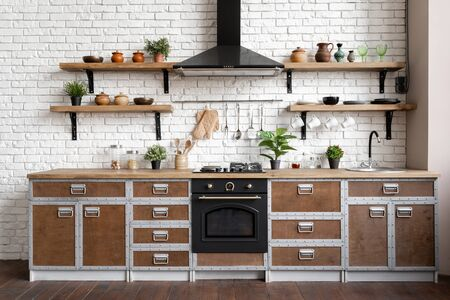 Wooden kitchen facade in apartment with modern interior, new furniture, gas stove, built in oven equipment, cooking hood, kitchenware supplies near sink and houseplant in flower pot