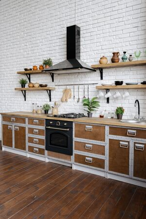 Side view of kitchen with gas stove, built in oven equipment, cooking hood, kitchenware supplies, houseplant in flower pot. Vertical view of wooden furniture in contemporary interior with copy space