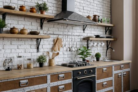 Side view of wooden kitchen with new furniture, water tap over sink, gas stove, built in oven equipment, cooking hood, kitchenware supplies, houseplant in flower pot in contemporary interior