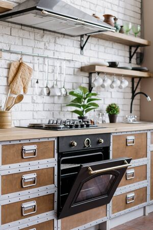 Vertical view of new furniture, gas stove, built in oven with open door, cooking hood equipment, kitchenware supplies and green houseplant decor. apartment with modern interior and wooden kitchen