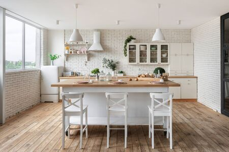 Tableware on dining table, kitchenware supplies on shelves, green plants on cupboard furniture and refrigerator. White kitchen in apartment with modern interior Imagens