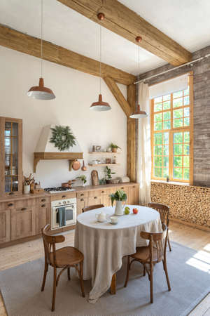 Side view photo of wooden kitchen with food, drinks and tablecloth on dinner table, cooking hood over gas stove, oven appliance, kitchenware supplies. Vertical photo of modern interior with furniture