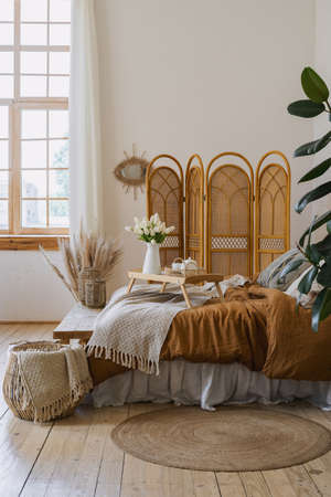 Concept on weekend morning. Vertical photo of cozy bedroom with authentic interior design, pillow, plaid and breakfast tray on bed, wooden bench seat, dressing screen, wicker basket Stockfoto