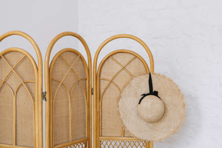 Element of cozy bedroom with authentic interior design, summer brimmed hat on bamboo dressing screen against white copy space wall