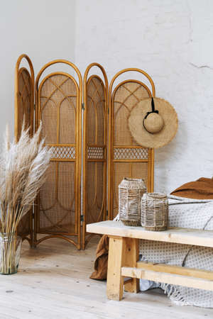 Vertical photo of comfort apartment in bohemian style interior with hygge bedroom, hat on bamboo dressing screen, dry plants in vase, home decor in wicker basket 免版税图像