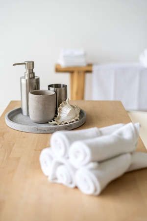 Selective focus on soap dispenser and house decor at wooden shelf on bath in bathroom. Vertical photo of clean and fresh rolled towels near beauty products in spa salon