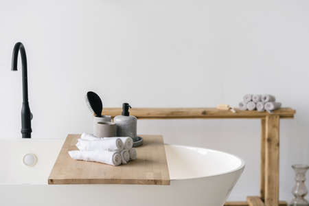 Hair brush, soap dispenser and clean fresh towels on wooden shelf over white contemporary bath with black faucet. Modern bathroom interior with bathtub and water tap