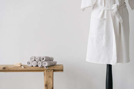 White cotton bathrobe near wooden bench with clean fresh rolled towels and nail brush. Beauty care products in bright modern bathroom or spa salon Reklamní fotografie