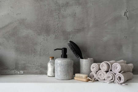 Close up of bottle with soap dispenser, hairbrush, bath salt, clean and fresh rolled towels near soft nail brush on shelf in bathroom against grey copy space wall on background Reklamní fotografie