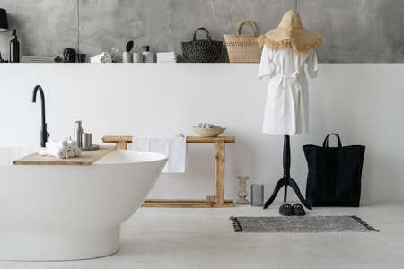 Element of white comfortable bath in modern house with contemporary interior design. Home decor, clean dry towels and bathrobe in apartment with bright bathroom Reklamní fotografie - 151446662