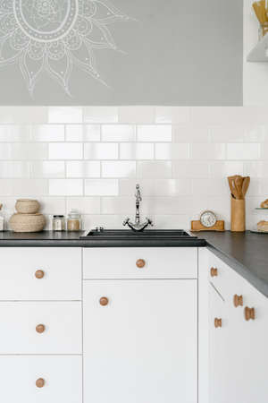 Vertical photo of white modern house with kitchen in tiled wall, drawers over cupboards, utensils near clock on countertop, sink and shiny water tap