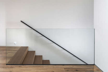 Element of modern interior design with hardwood stairs and glass fence against white copy space wall Standard-Bild
