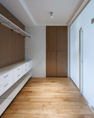 Empty wooden wardrobe closet with shelves and drawers in dressing room. Vertical view of modern house with contemporary interior design in bedroom