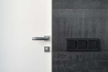 Element of modern interior design with electric light switch on black copy space wall near minimalist handle on closed white door
