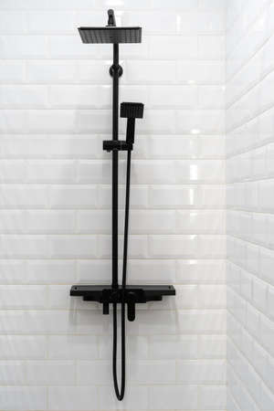 Vertical photo of white bathroom in modern apartment. New black shower head on holder against clean tiled wall on background Standard-Bild