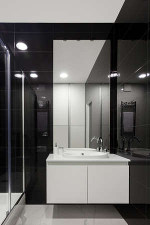 Shower cabin and wash basin on countertop under mirror, heated towel rail, against black white tiled wall. Vertical view of modern house with contemporary interior design in bathroom